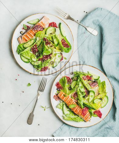 Healthy energy boosting spring salad with grilled salmon, blood orange, olives and quinoa, top view, marble background. Clean eating, dieting, detox, weight loss concept