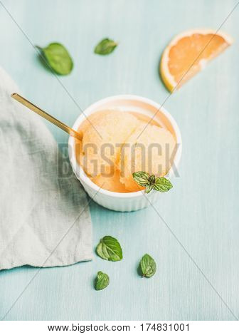 Pink grapefruit sorbet with fresh mint leaves in white bowl over blue painted background, selective focus. Fresh healthy raw vegan summer dessert concept
