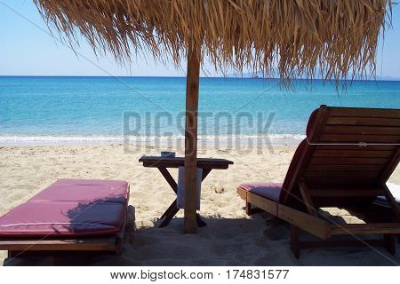 Idyllic sun umbrella and two empty deckchairs with a sea view on Mykonos island Greece