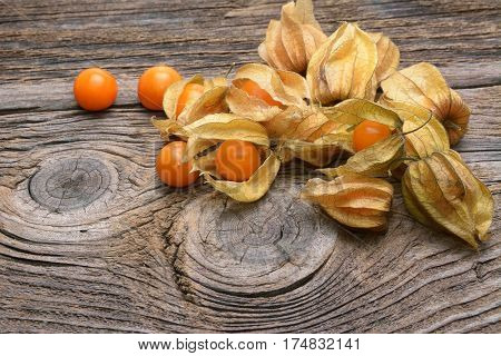 Physalis fruit isolated over old wood table