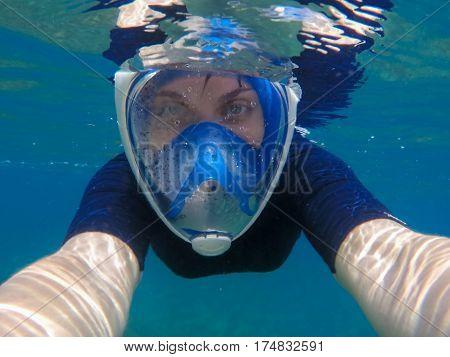Woman selfie underwater. Young girl swimming under water in modern snorkeling gear. Full-face snorkeling mask. Tropical sea sport activity. Summer vacation in exotic island. Female snorkel undersea