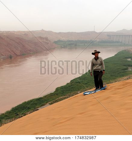Ningxia, China - Jul 9, 2011: Chinese Man Going To Slide Down The Sand Hill At The Bank Of Yellow Ri