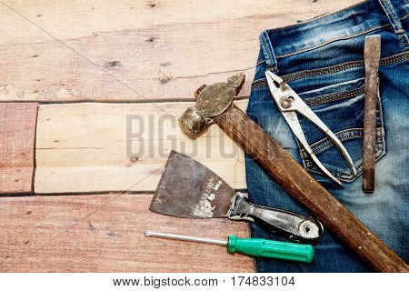 Tools hammer, putty knife, screwdriver and old blue jeans on a wooden background. Concept of repair and construction