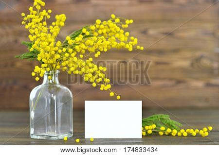 Mothers Day card and mimosa on wooden background