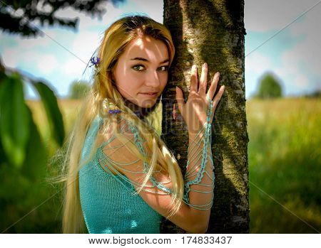 Young girl with long blond hair hugging tree trunk
