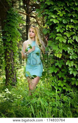 Pretty young blonde girl with long hair in turquoise dress standing in the green forest where trees are enlaced with lianas