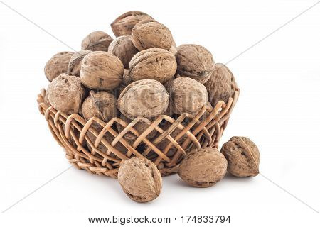 Dried walnuts in woven basket, on a white background