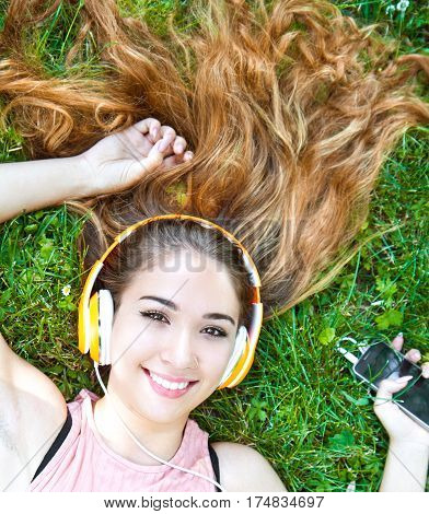 Girl listening to music streaming with headphones in summer