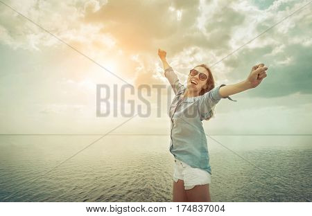 Happy woman relaxation on the sunny sea beach under sunlight sky with clouds at summer day, travel vacation, landscape beach background