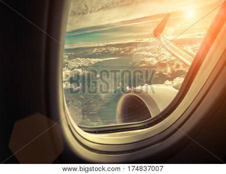 Beautiful view from  porthole of airplane on sky with clouds under sun light. View from at sunny day.