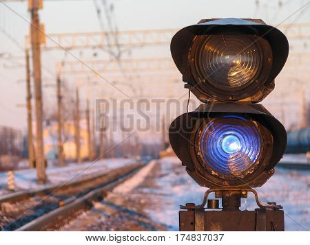 Railway traffic light shows blue signal on railway.