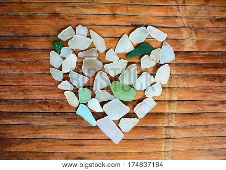 Seashore glass pebble heart on wooden background. Sugar glass mosaic for Valentine's Day. Romantic shabby chic decor. Seaside greetings for Valentine Day. Beach glass on grungy wood. Sea trash recycle