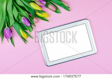 Top view of tablet and flowers. Spring composition with tulips. Space for copy