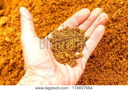 Men's hand showing sand on a background of sand