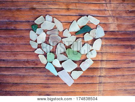 Seashore glass pebble heart on wooden background. Sugar glass mosaic for Valentine's Day. Romantic shabby chic decor. Seaside greetings for Valentine Day. Beach glass on grungy wood backdrop. Sea care