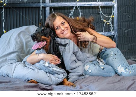 Pretty Woman in bed with big black doberman dog