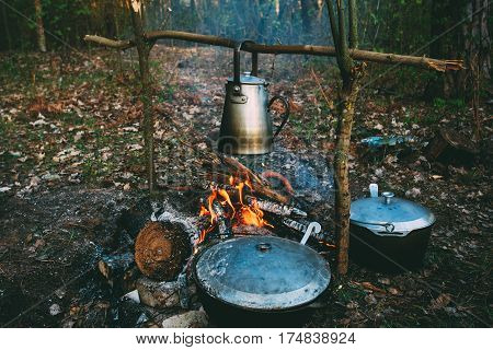 Old Retro Iron Camp Kettle And Pans Boils Water On A Fire In Forest. Bright Flame Fire Bonfire At Dusk Night.