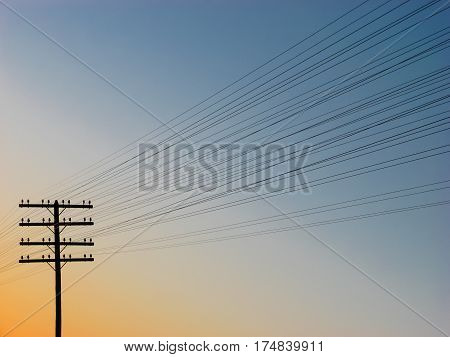 Silhouette of power-transmission pole with wires during sunset
