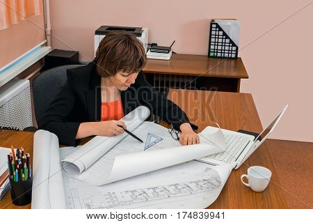 Woman engineer draws drawings. Workplace of architect. Design.