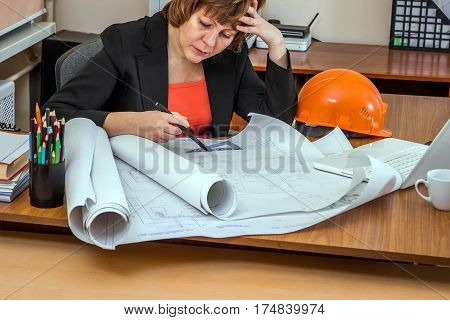 Woman engineer in search of solutions. She looking at the drawings. Head propped hand.