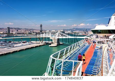 Barcelona Spain - June 7 2016: Cruise ship passengers stroll around the Lido Deck on a cruise ship anchored in port in Barcelona Spain.