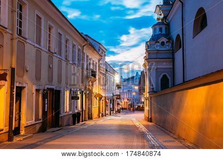 Vilnius, Lithuania. The View Of Deserted Illuminated Ausros Vartu Street, The Ancient Famous Showplace Of Old Town In Summer Twilight Under Blue Sky.