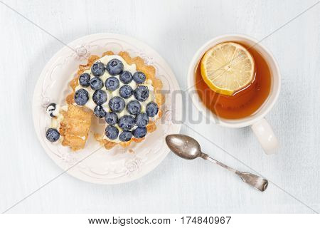 Sweet cake with blueberries butter cream and syrup as well as a cup of black tea with a slice of lemon top view