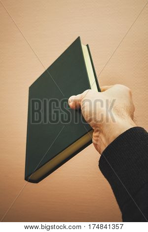 Male Hand Holds Dark Green Book