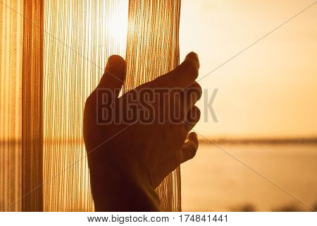 Hand Opens Tulle On Window With Sunlight