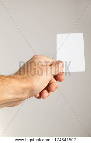 Hand With White Empty Card Over Gray