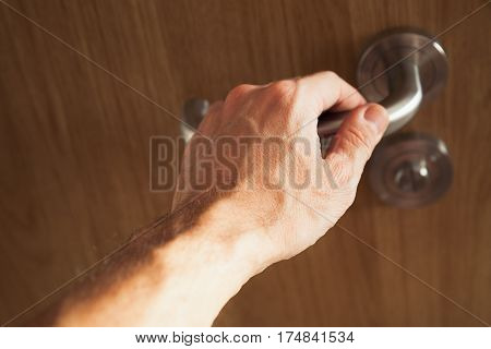 Male Hand Opens Wooden Door