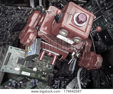 red robot buried in old electronics