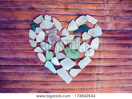 Seashore glass heart on wooden background. Sugar glass mosaic for Valentine's Day. Romantic shabby chic decor. Seaside greetings for Valentine Day. Beach glass on grungy wood . Ecology care concept