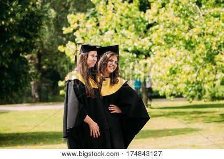 Riga, Latvia - July 1, 2016: Two young women graduates of the University of Latvia dressed in gown graduates and Square academic caps posing for photos.