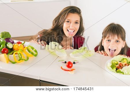 Funny family making smiley face with salad. Cooking vegetarian meal at kitchen. Funny sisters making salad. Healthy lifestyle. Recipe of vitamins nutrition. Girls looking at camera
