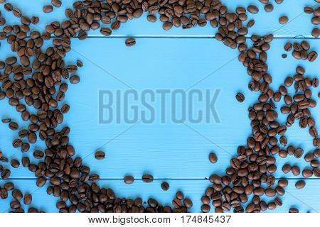 empty frame of roasted beans on the background of blue wooden plank top view / coffee background gourmet