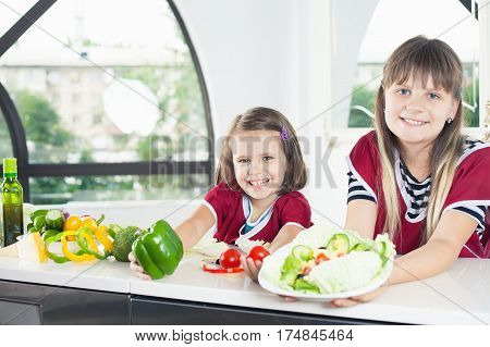 Cute little girl cooking with her sister. Healthy food, cooking healthy salad with vegetables ingredients. Daughters cooking together. Recipe food for baby or child