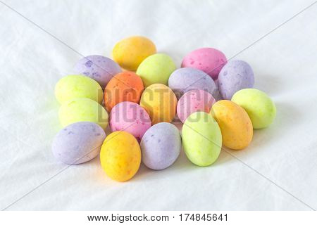 Spring colorful chocolate easter eggs sitting in a white sheet all together in a bunch