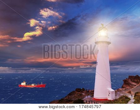 Sunset seascape, lighthouse on the bluff