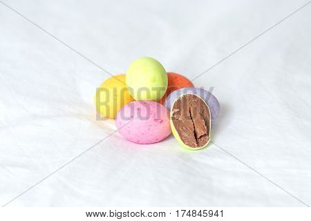 Spring colorful easter eggs sitting in a white sheet with one cutted in half showing it's milky brown creamy chocolate.