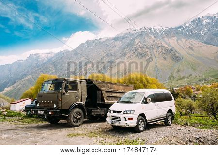 Stepantsminda, Georgia - May 22, 2016: Old Soviet Russian medium-duty truck Kamaz 53212 and SUV Mitsubishi Delica Space Gear parking together in village on summer mountains landscape in Georgia.