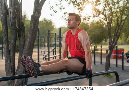 Fit man performing leg raises on outdoor fitness station