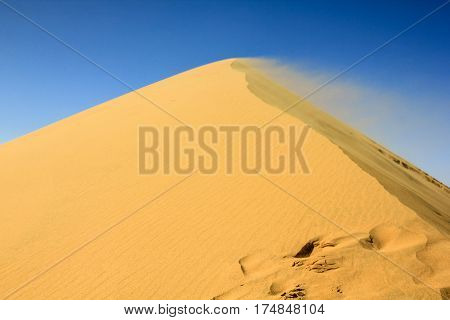 Sand blowing off the top of a dune in the desert. Namib-Naukluft National Park, Namib Desert, Namibia, Africa.