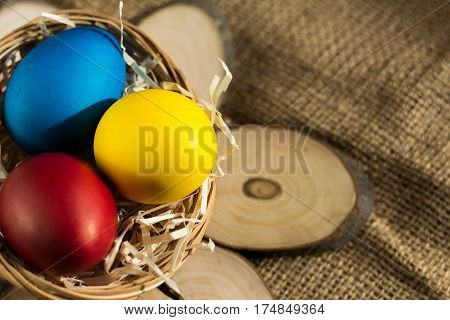 Colored Easter eggs in a basket on a rustic background