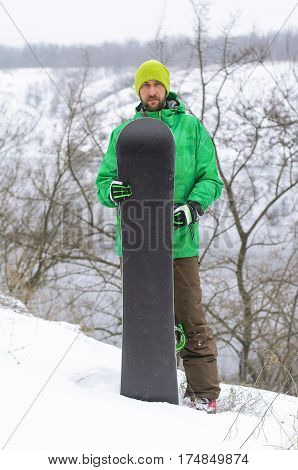 Snowboarder In Bright Clothes Posing With A Snowboard.