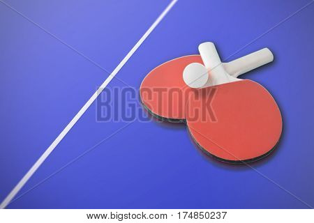 Ping pong paddles and a ball on a blue table. Empty copy space for Editor's content.
