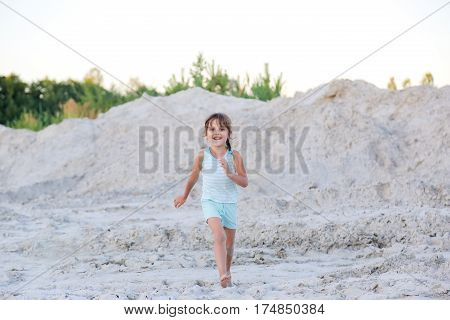 Little girl plays in the sand and looking at the camera.
