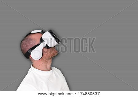 A man using a Virtual Reality VR glasses against an empty background. Empty copy space for Editor's content.