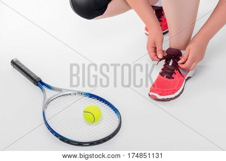 Woman Tying Shoelaces Before A Game Of Tennis On A White Background