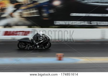 Slow Shutter Speed Shot Of A Motorcycle Accelerating Down A Race Track